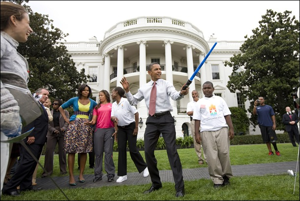 President Barack Obama uses a light saber as he watches a demonstration of fencing at an event supporting Chicago's 2016 host city Olympic bid, on the South Lawn of the White House in Washington. At rear is Chicago Mayor Richard Daley and first lady Michelle Obama.  Photo by Brooks Kraft/Corbis